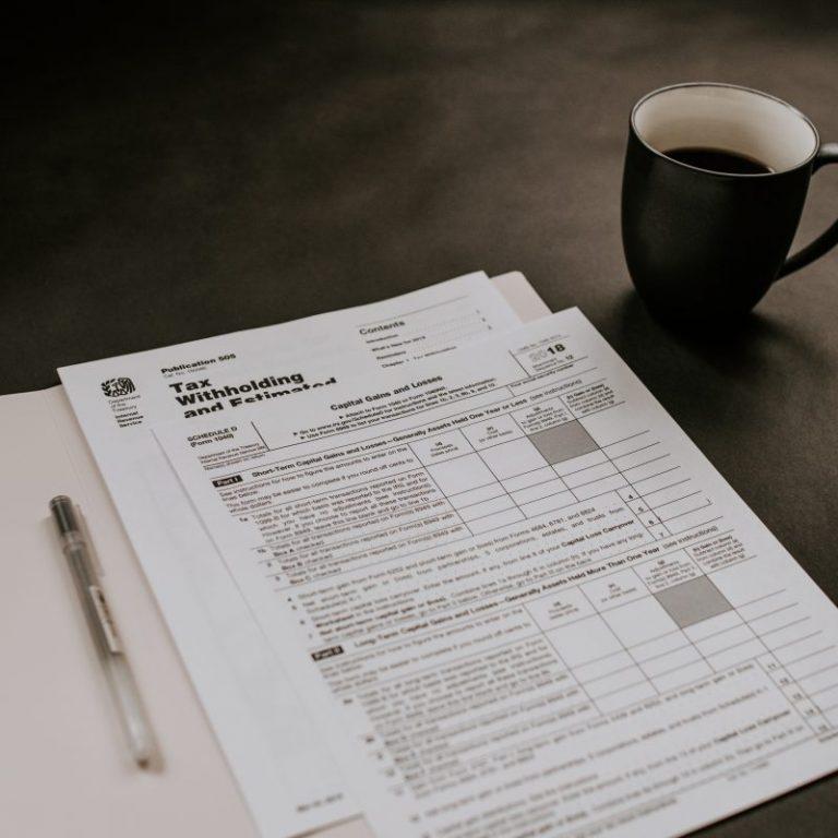 black ceramic mug beside white printer paper