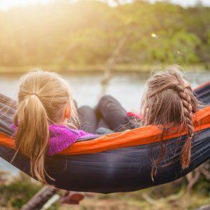 two women lying on hammock