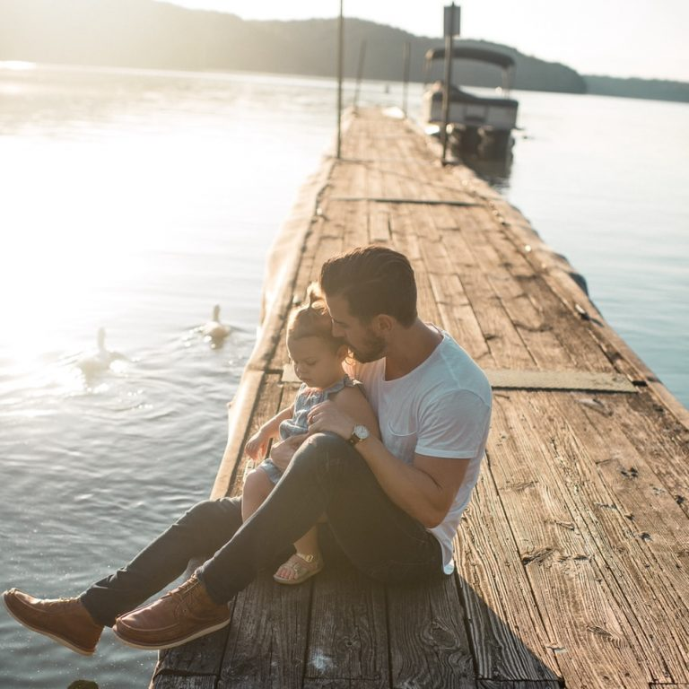 man and girl sitting on brown dock near boat and two white ducks during daytime