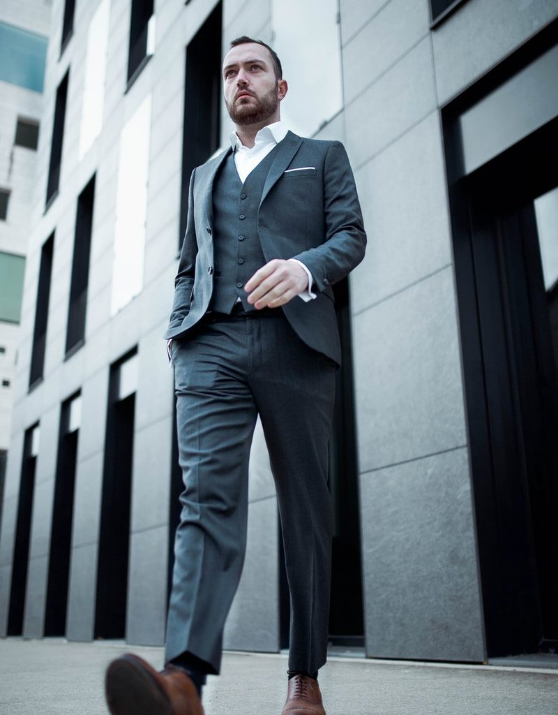 man in blue suit standing near white concrete building during daytime