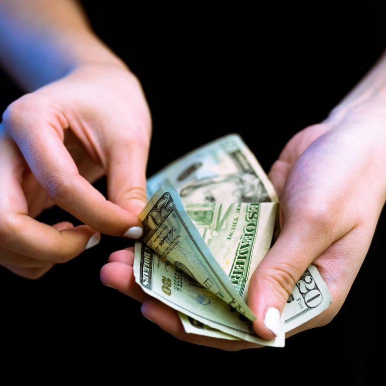 person holding fan of 100 us dollar bill